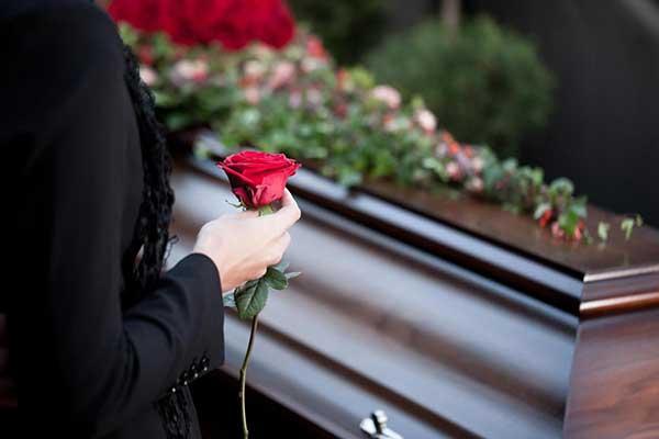 Kukka pitelevän naisen käsi arkun edessä